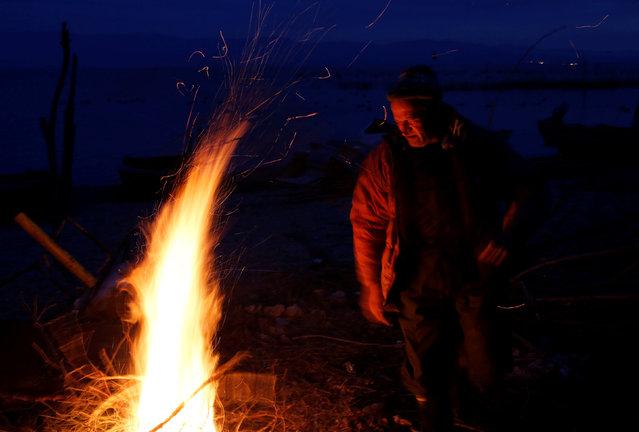 A fisherman warms by the fire at Dojran Lake, Macedonia, January 4, 2017. (Photo by Ognen Teofilovski/Reuters)
