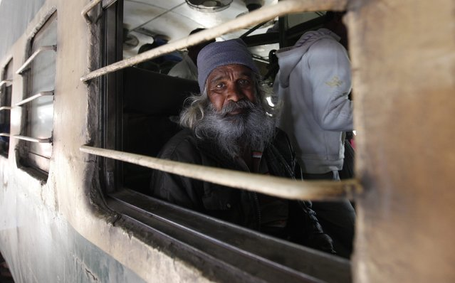A fisherman from India sits in train while being photographed, after his release with others from a prison, at Karachi's Cantonment railway station, February 15, 2015. (Photo by Akhtar Soomro/Reuters)