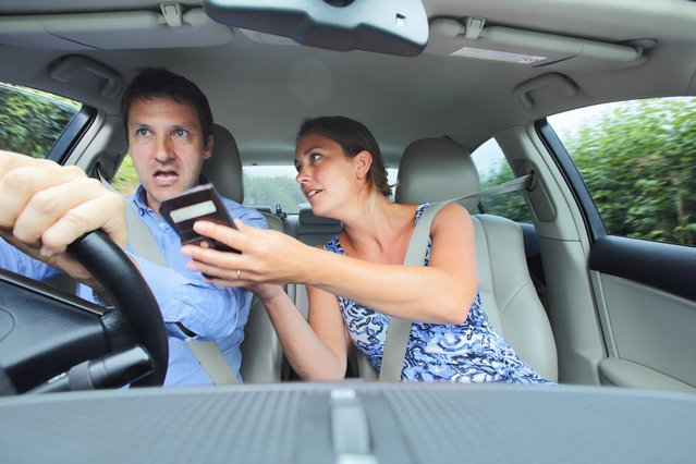 Couple arguing in car, woman showing man phone. (Photo by Peter Cade/Getty Images)