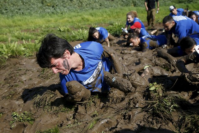 An Israeli teenager crawls through mud as he participates in an annual combat fitness training competition, as part of his preparations ahead of his compulsory army service, near Kibbutz Yakum, central Israel February 19, 2016. (Photo by Baz Ratner/Reuters)
