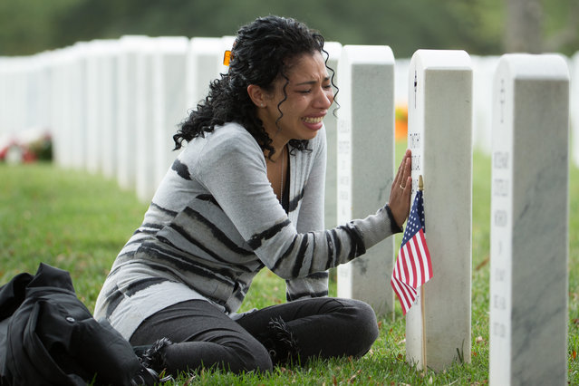 Thania Sayne of Effingham, Ill., cries at the grave of her husband, Army Sgt. Timothy D. Sayne, during the playing of taps at a nearby burial service at Arlington National Cemetery, in Arlington, Va., Wednesday, October 16, 2013, a day before what would have been their third wedding anniversary. (Photo by Manuel Balce Ceneta/AP Photo)