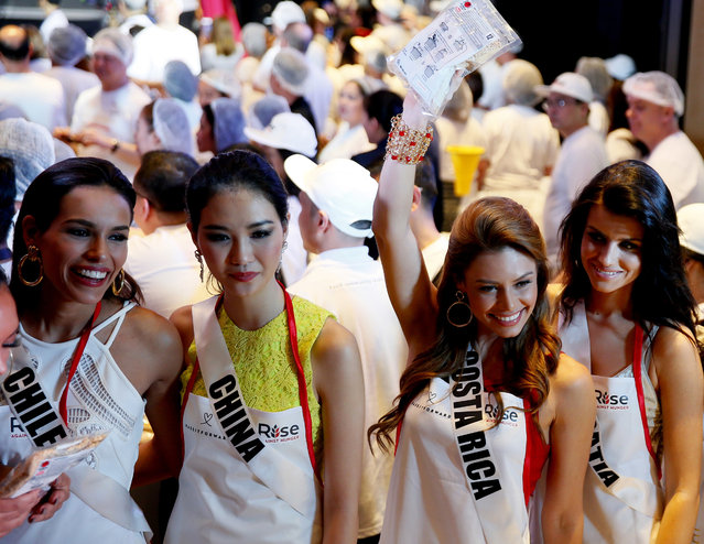 Miss Universe contestants, from left; Catalina Paz Caceres of Chile, Li ZhenYing of China, Carolina Duran of Costa Rica and Barbara Filipovic of Croatia, pose before helping out pack meals for an NGO for distribution to the needy in suburban Pasay city southeast of Manila, Philippines Wednesday, January 18, 2017. (Photo by Bullit Marquez/AP Photo)