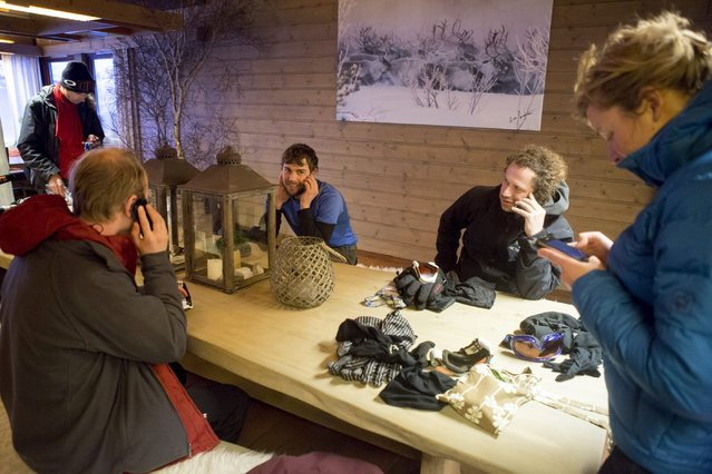 Rescued Dutch hikers use their mobile phones to call their families after they were brought safely to a hotel in Grotli, Norway, February 26, 2016. (Photo by Torstein Boe/Reuters/NTB Scanpix)