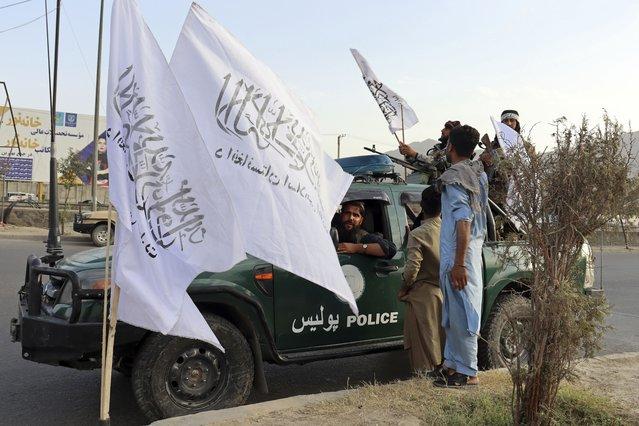 Taliban fighters buy Taliban flags in Kabul, Afghanistan, Monday, August 30, 2021. (Photo by Khwaja Tawfiq Sediqi/AP Photo)