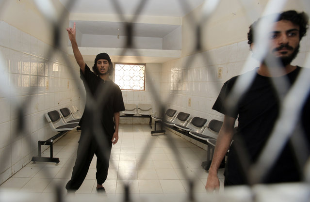 Mansour Dalil (L), an al-Qaeda suspect, reacts after a verdict was announced at a state security court sentencing him to death in Sanaa, Yemen, July 7, 2010. The court sentenced Dalil and co-defendant Mubarak al-Shabwani (R) to death for killing senior security officers in attacks last year. (Photo by Khaled Abdullah/Reuters)