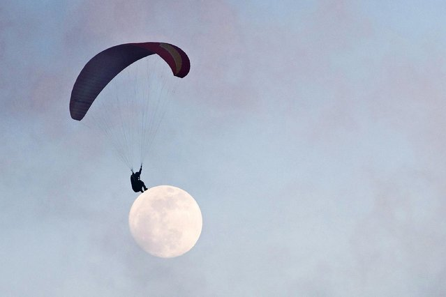 In this photo taken on December 21, 2018, the moon is seen in the distance past a paraglider near Ma On Shan peak in Hong Kong. With most young Hong Kongers priced out of the city's eye-watering property market – often living with parents in cramped flats well into their thirties – paragliding is one of a number of outdoor sports that offers release from the stress of the concrete jungle below. (Photo by Anthony Wallace/AFP Photo)