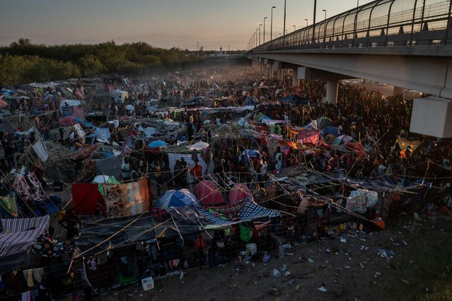 Migrants take shelter along the Del Rio International Bridge at sunset as they await to be processed after crossing the Rio Grande river into the U.S. from Ciudad Acuna in Del Rio, Texas, U.S. September 19, 2021. Picture taken with a drone. (Photo by Adrees Latif/Reuters)