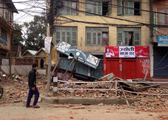 An  man walks past damage caused by an earthquake in Kathmandu, Nepal, Saturday, April 25, 2015. (Photo by Niranjan Shrestha/AP Photo)