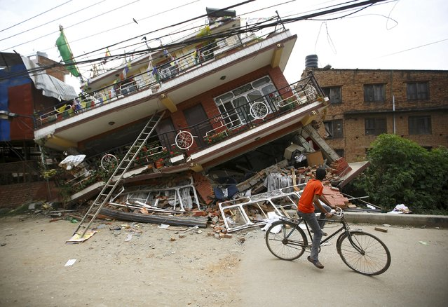 A boy riding a bicycle looks at a collapsed house after Saturday's earthquake, in Kathmandu, Nepal April 28, 2015. (Photo by Navesh Chitrakar/Reuters)