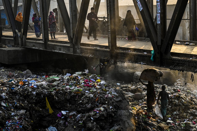 A Bangladeshi woman (lower R) carries recyclable waste over piles of trash underneath a pedestrian bridge in Dhaka on January 23, 2019. (Photo by Munir Uz Zaman/AFP Photo)