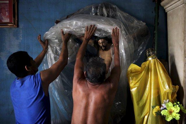 A 150-year-old statue of El Jesus Nazareno is unwrapped by members of the Santa Catarina brotherhood in Izalco, El Salvador, March 11, 2016. (Photo by Jose Cabezas/Reuters)