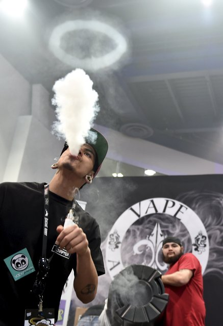 Angel Huezo (L) blows a plume of vapor through a vapor ring created by Bodie Hultz at the Vape Summit 3 in Las Vegas, Nevada May 2, 2015. (Photo by David Becker/Reuters)