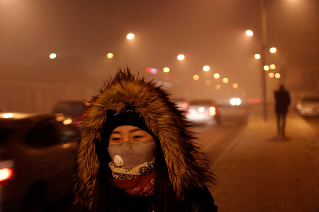 A woman wears a face mask in the part of the city near neighbourhoods known for burning coal for heating in Ulaanbaatar, Mongolia January 26, 2017. Not many people in Ulaanbaatar wear masks to protect themselves against pollution. (Photo by B. Rentsendorj/Reuters)