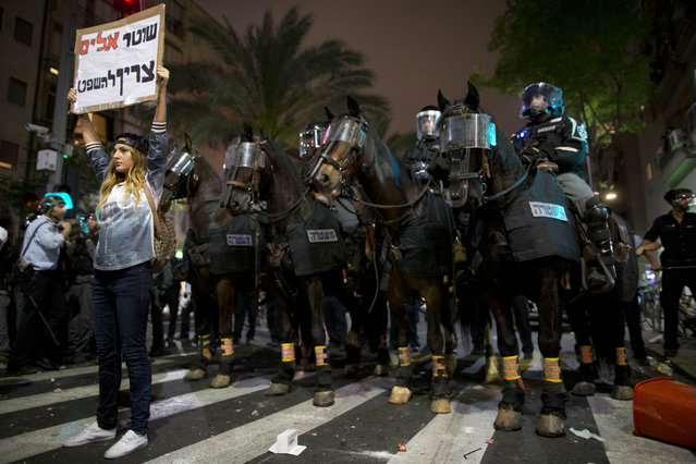"An Israeli protester holds a sign in Hebrew reading ""violent policeman should be sentenced"" during clashes between Israel's, mainly Jewish Ethiopians and Israeli riot police during a protest against racism and police brutality in Tel Aviv, Israel, Sunday, May 3, 2015, as several thousand people from Israel's Jewish Ethiopian minority protest, shutting down a major highway and clashing with police on horseback long into the night. (Photo by Oded Balilty/AP Photo)"