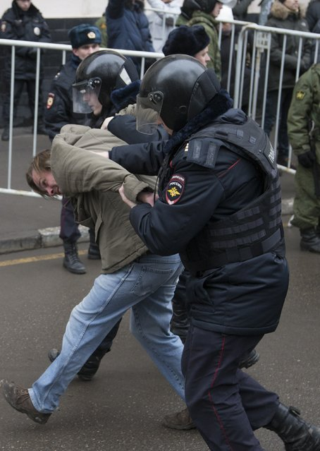 Russian police officers detain an opposition activist outside a court room in Moscow, Russia, Monday, February 24, 2014. (Photo by Alexander Zemlianichenko/AP Photo)