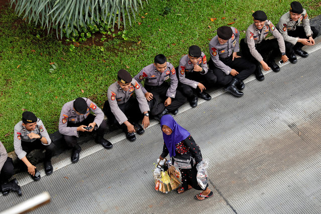 A street vendor carries her goods as Indonesian police officers rest during a May Day rally near the National Monument (Monas) in Jakarta, Indonesia, May 1, 2019. (Photo by Willy Kurniawan/Reuters)