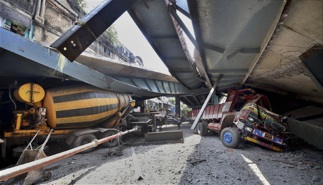 Vehicles are seen trapped under a partially collapsed overpass in Kolkata, India, Thursday, March 31, 2016. (Photo by Swapan Mahapatra/Press Trust of India via AP Photo)