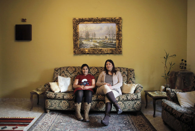 Hala Tanmus, 40, and her daughter Maya, 10, pose for a picture in the living room of their home in the West Bank city of Ramallah February 18, 2014. Hala is a secretary who finished her education at age 20. When she was younger she wanted to become a lawyer. She hopes that her daughter Maya will become an interior designer. Maya, who says she will finish education age 20, would also like to become an interior designer. (Photo by Ammar Awad/Reuters)
