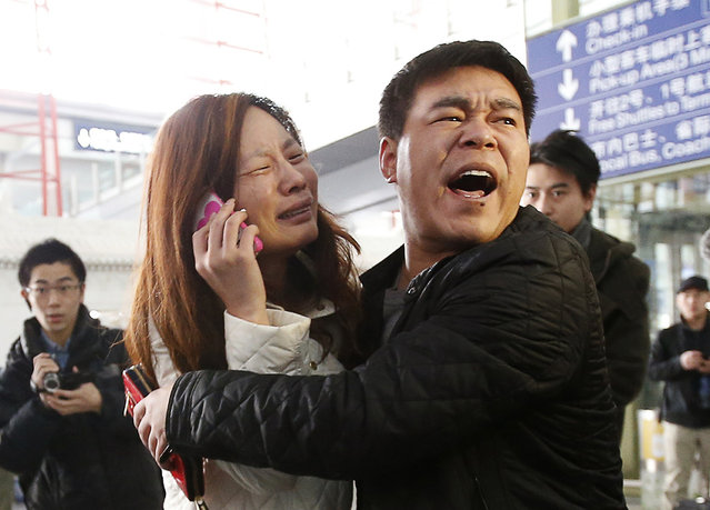 A relative (woman in white) of a passenger onboard Malaysia Airlines flight MH370 cries as she talks on her mobile phone at the Beijing Capital International Airport March 8, 2014. The Malaysia Airlines flight carrying 227 passengers and 12 crew lost contact with air traffic controllers early on Saturday en route from Kuala Lumpur to Beijing, the airline said in a statement. (Photo by Kim Kyung-Hoon/Reuters)