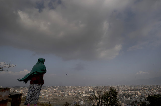A mother stands on a windy hillside overlooking the capital as she waits for her child's school bus arriving in the outskirts of Kathmandu, Nepal, 18 February 2019. According to publicly available reference data dated from 2015, Nepal spent 3.7 percent of its Gross Domestic Product (GDP) for education and has a literacy rate of around 64 percent of the population of an estimate 30 million. (Photo by Narendra Shrestha/EPA/EFE)