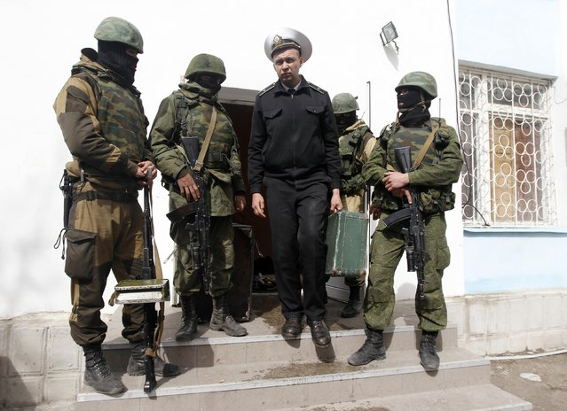 A Ukrainian naval officer passes by armed men, believed to be Russian servicemen, as he leaves the naval headquarters in Sevastopol. A communications specialist in the Ukrainian navy who was outside the base when the assault began said a truck rammed the gate and about 200 men with AK-47 rifles stormed the facility, a collection of office buildings in the center of Sevastopol. The Ukrainians inside initially tried to barricade themselves but could not hold out, he said. (Photo by Vasily Fedosenko/Reuters)