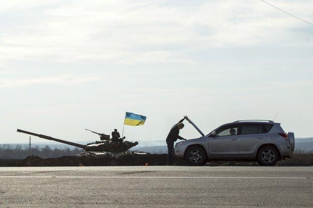 A motorist checks his car next to a tank position close to the Russian border near the Ukrainian city of Kharkiv March 24, 2014. (Photo by Dmitry Neymyrok/Reuters)