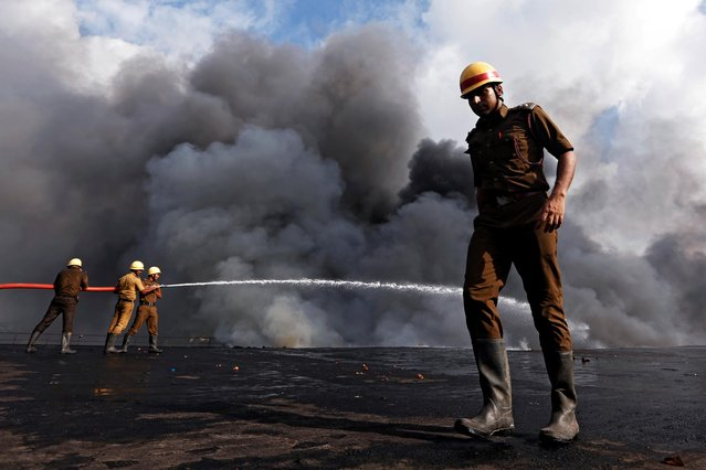 Firefighters try to douse a fire that broke out at a chemical and a cloth warehouse on the banks of river Ganges in Kolkata, India June 8, 2019. (Photo by Rupak De Chowdhuri/Reuters)