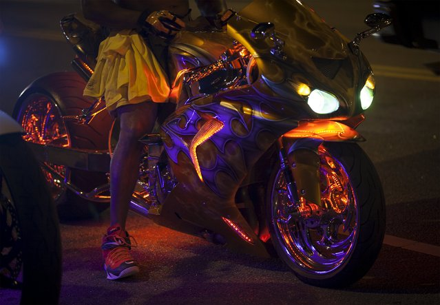 A customized sport bike is lit in neon lights as it's driver waits in traffic on Ocean Boulevard during the 2015 Atlantic Beach Memorial Day BikeFest in Myrtle Beach, South Carolina May 24, 2015. (Photo by Randall Hill/Reuters)