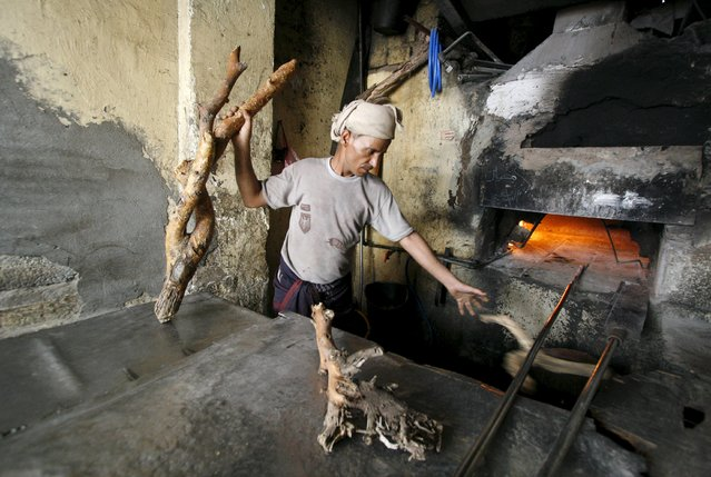 A baker uses firewood amid an acute fuel shortage in Yemen's southwestern city of Taiz May 19, 2015. Lack of diesel has forced owners of diesel-fueled businesses including bakeries to look for other alternatives sources of fuel. (Photo by Reuters/Stringer)