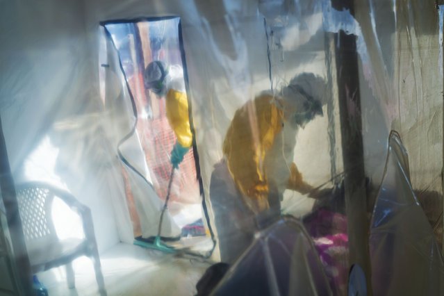In this photograph taken Saturday 13 July 2019, health workers wearing protective suits tend to to an Ebola victim kept in an isolation cube in Beni, Congo DRC. The Congolese health ministry is confirming the country's first Ebola case in the provincial capital of 2 million, Goma, some 360 kms ( 225 miles) south of Beni. More than 1,600 people in eastern Congo have died as the virus has spread in areas too dangerous for health teams to access. (Photo by Jerome Delay/AP Photo)
