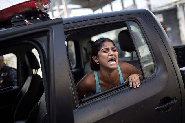 A woman screams after being detained during protests near the area recently occupied by squatters in Rio de Janeiro on April 11, 2014; she was later released.  (Photo by Felipe Dana/Associated Press)