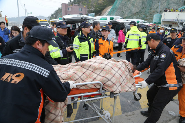 A rescued passenger from a ferry sinking off South Korea's southern coast, is carried by rescue teams on his arrival at Jindo port in Jindo, south of Seoul, South Korea, Wednesday, April 16, 2014. (Photo by Park Chul-heung/Reuters/Yonhap)