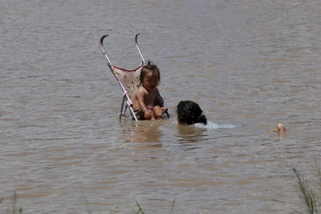 A woman bathes a girl seated in a stroller in Rio Bravo during a hot summer day at the border crossing between Mexico and the United States in Ciudad Juarez, Mexico, June 28, 2015. (Photo by Jose Luis Gonzalez/Reuters)