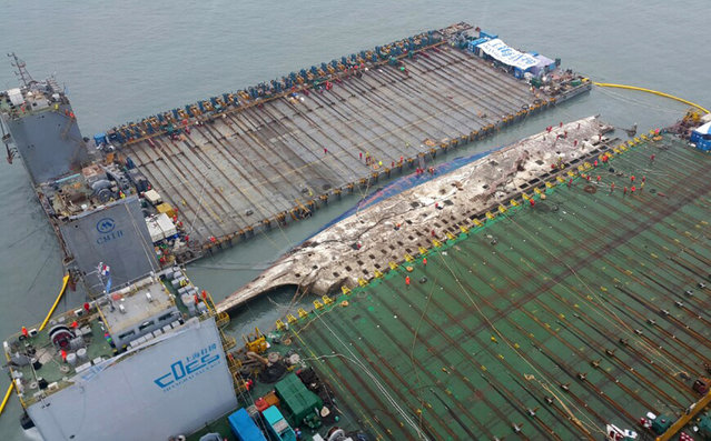 In this photo provided by West Regional Headquarters Korea Coast Guard, workers prepare to lift the sunken Sewol ferry, center, in waters off Jindo, South Korea, Thursday, March 23, 2017. A 6,800-ton South Korean ferry emerged from the water on Thursday, nearly three years after it capsized and sank into violent seas off the country's southwestern coast, an emotional moment for the country that continues to search for closure to one of its deadliest disasters ever. (Photo by West Regional Headquarters Korea Coast Guard via AP Photo)