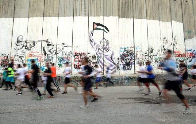Participants run past the Israeli barrier during the annual Palestine Marathon in the West Bank town of Bethlehem March 31, 2017. (Photo by Ammar Awad/Reuters)