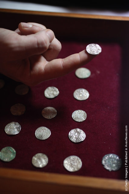 An employee of the British Museum examines a silver coin dating from 900 AD which is part of the Silverdale Viking Hoard