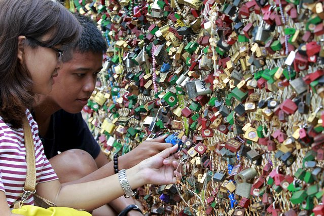 A couple puts a padlock on a fence as they pray for a lasting relationship and ask for blessings, in front of a Catholic church in Paranaque city, metro Manila, Philippines July 4, 2015. (Photo by Romeo Ranoco/Reuters)