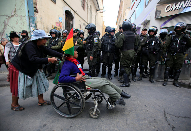 A demonstrator with physical disabilities, helped by a relative, passes in front of riot policemen during a rally protest calling on the government to provide a monthly subsidy rather than an annual one, in La Paz, Bolivia, May 5, 2016. (Photo by David Mercado/Reuters)