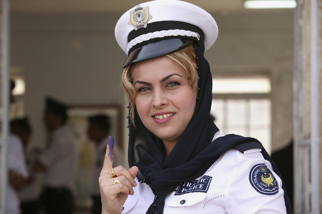 A traffic policewoman shows her ink-stained fingers after casting her ballot at a polling station, during early voting for the parliamentary election in the northern Iraqi province of Dohuk, April 28, 2014. Iraq will be holding its national elections on April 30. (Photo by Ari Jala/Reuters)