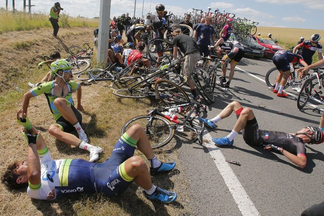 Scores of riders lie on the road after crashing during the third stage of the Tour de France cycling race over 159.5 kilometers (99.1 miles) with start in Antwerp and finish in Huy, Belgium, Monday, July 6, 2015. (Photo by Christophe Ena/AP Photo)