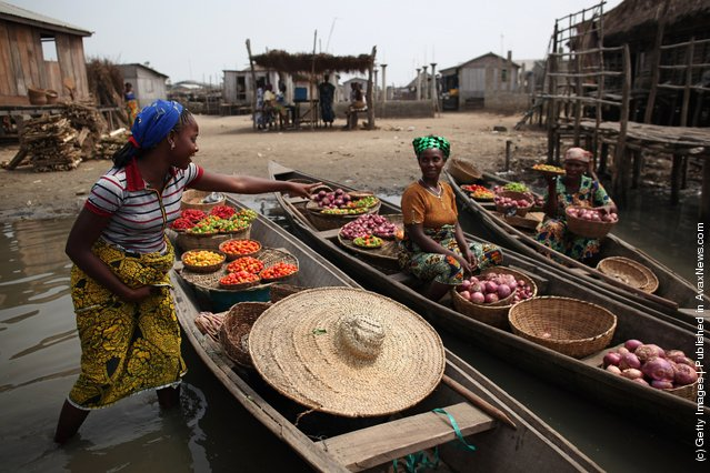 Produce including peppers, tomatoes and chillis are brought to shore by women in Ganvie, near Cotonou, Benin
