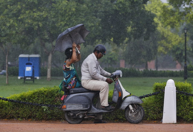 A commuter prepares to park his scooter as his passenger holds an umbrella during a heavy rain shower in New Delhi, India, June 22, 2015. (Photo by Adnan Abidi/Reuters)