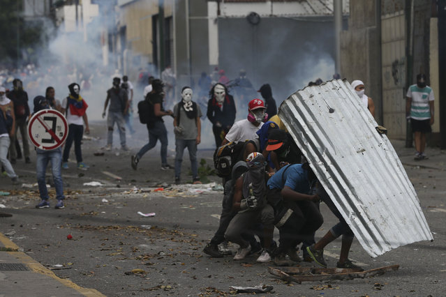Demonstrators take cover with a piece of corrugated tin roofing during anti-government protests in Caracas, Venezuela, Wednesday, April 19, 2017. (Photo by Fernando Llano/AP Photo)
