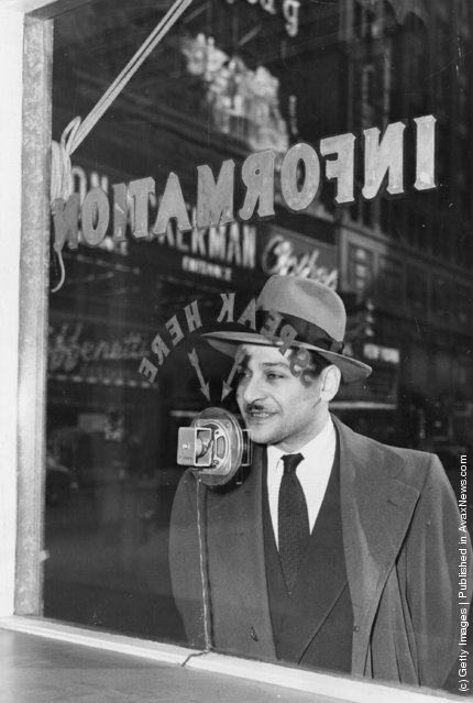 1949: An information seeker speaks into a microphone at a police information booth at Times Square, New York