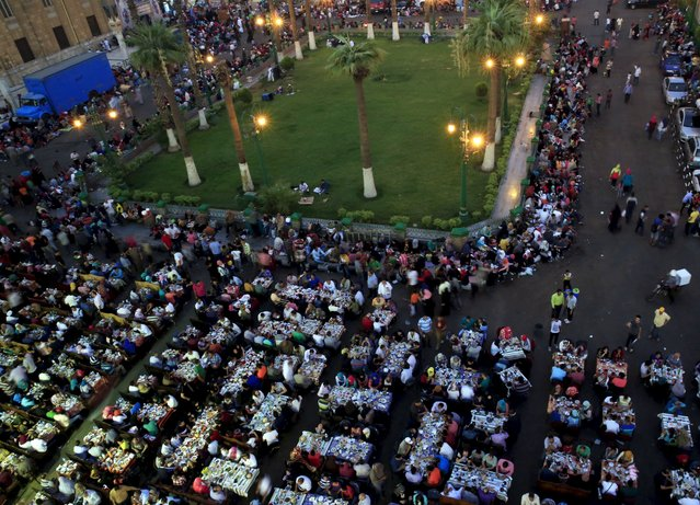 People eat their Iftar meal as they break their fast around the garden of Al-Hussein mosque during the holy fasting month of Ramadan, in the old Islamic area of Cairo, Egypt, July 9, 2015. (Photo by Amr Abdallah Dalsh/Reuters)