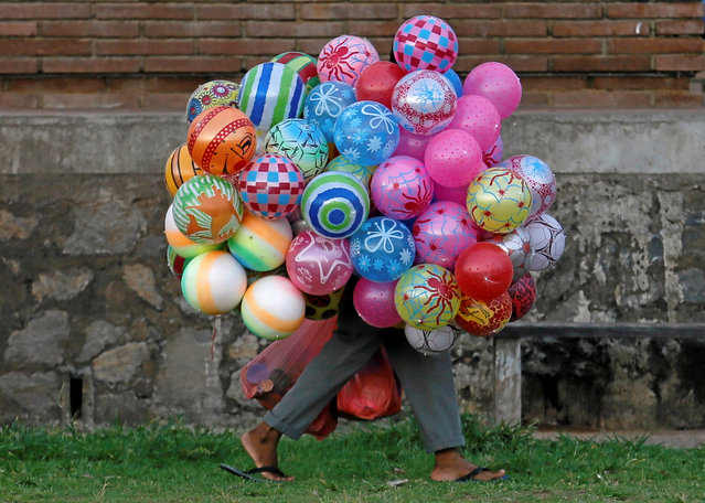 A vendor carries a bunch of balloons as he looks for customers in Colombo, Sri Lanka May 13, 2016. (Photo by Dinuka Liyanawatte/Reuters)