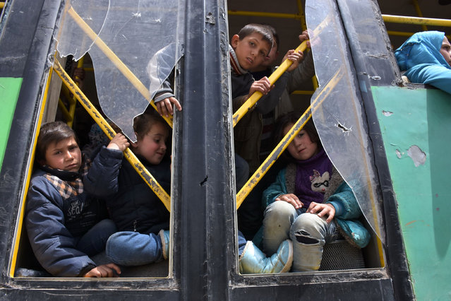 Young Syrians, evacuated from the two besieged government- held towns of Fuaa and Kafraya, arrive at a makeshift shelter in Jibrin on the eastern outskirts of Aleppo, on April 21, 2017. (Photo by  George Ourfalian/AFP Photo)