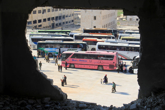 Syrians from the government- held towns of Fuaa and Kafraya, which have been under crippling siege for more than two years, reach with buses the edge of the rebel- held transit point of Rashidin outside government- held second city Aleppo, on April 19, 2017. The evacuation of civilians and fighters from besieged Syrian towns resumed after a weekend bombing at a transit point killed 126 people, 68 of them children, an AFP correspondent reported. (Photo by Omar Haj Kadour/AFP Photo)