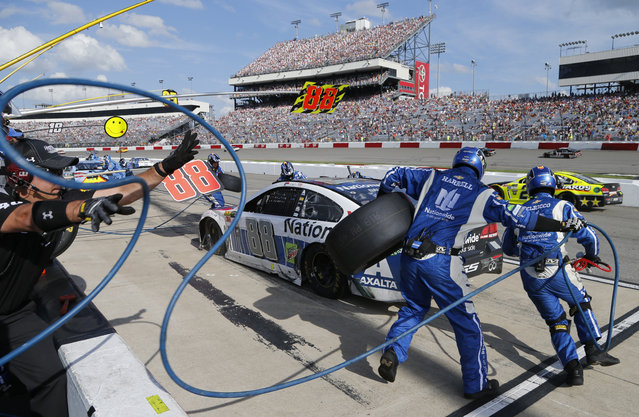 The pit crew for Dale Earnhardt Jr. (88) services his car during the NASCAR Cup Series auto race at Richmond International Raceway in Richmond, Va., Sunday, April 30, 2017. (Photo by Steve Helber/AP Photo)