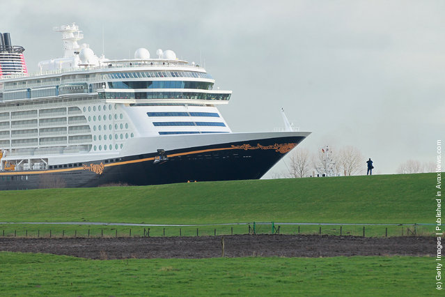 """Tugboats haul the """"Disney Fantasy"""" cruise ship backwards down Ems river after the ship departed from the Meyer Werft shipyards"""